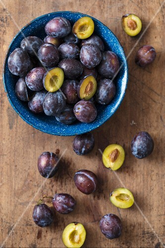 Fresh plums in a bowl and next to it on a wooden surface (seen from above)