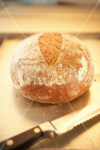 A loaf of potato bread next to a bread knife