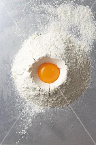 Egg yolks in heap of flour