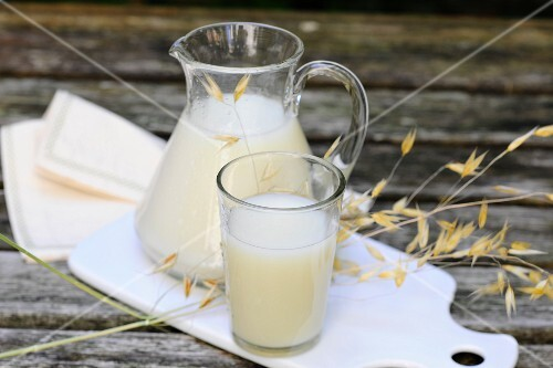 Oat milk in a glass and a jug