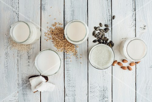 Various types of vegan milk in glasses next to almonds, rice, oats, pumpkin seeds and coconut