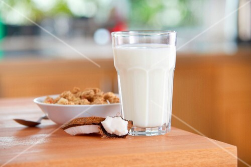 A glass of coconut milk, coconut pieces and cereals