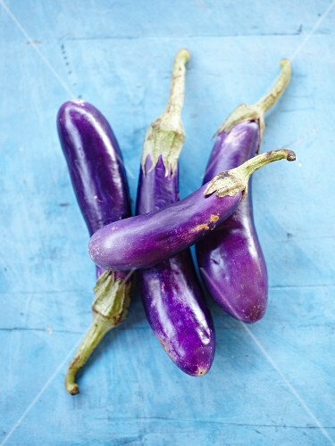 Aubergines on a blue surface