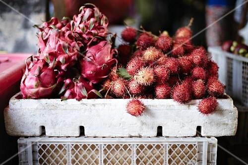 Pitahayas and rambutans in crates at a market