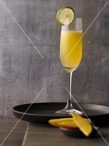 A champagne cocktail with mango and limes