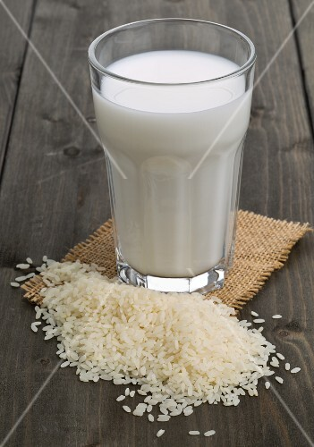 A glass of rice milk behind a pile of rice