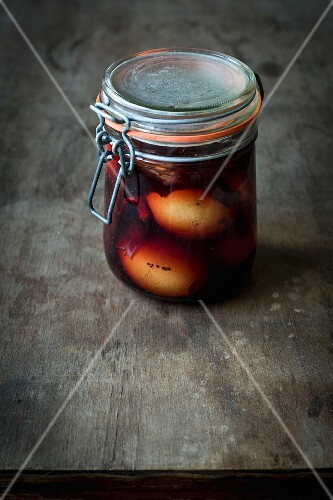 Pickled eggs with onion skins and a spiced liquid in a jar on a wooden table