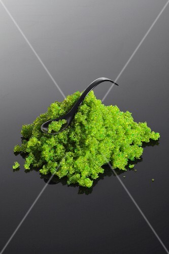 Green tobiko caviar from flying fish with a spoon