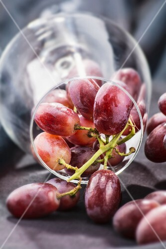 Red grapes in an overturned wine glass