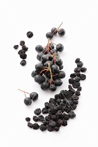 Fresh and dried aronia berries on a wooden surface