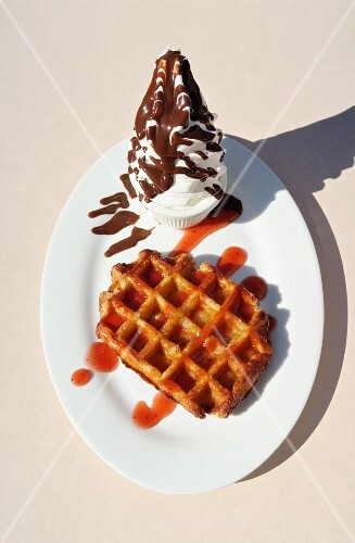 A Belgian waffle with strawberry sauce and soft ice with chocolate glaze