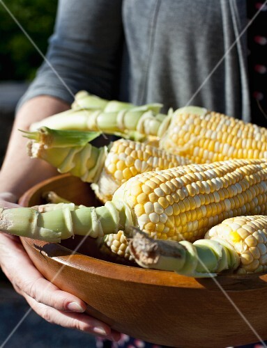 A woman holding a wooden bowl of corn cobs