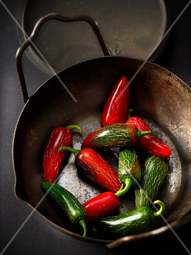 Red and green chilli peppers in an iron pot