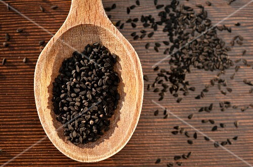 Black caraway seeds on a wooden spoon (seen above)