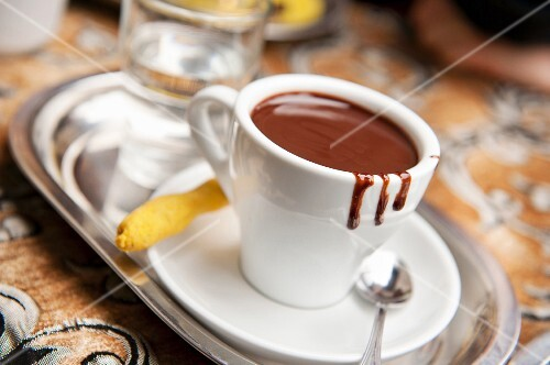 A cup of hot chocolate with a biscuit and a glass of water on a silver tray