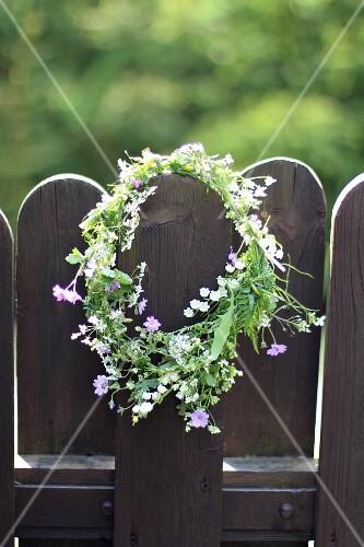 Spring wreath hanging on garden fence