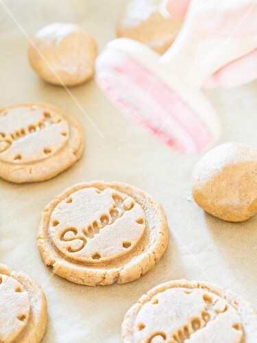 Unbaked cardamom biscuits stamped with the word 'Sweet'
