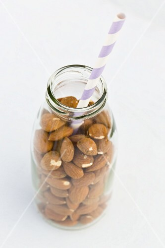 Almonds in a milk bottle with a straw