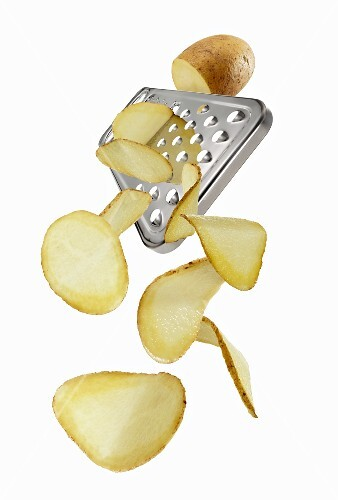A vegetable grate with a potato and potato slices