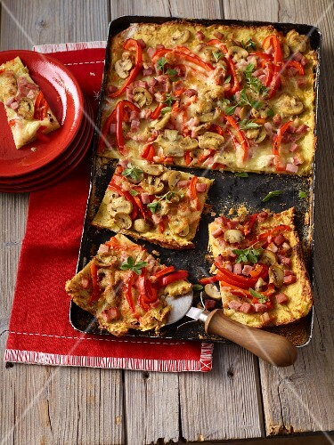Potato pizza with peppers, ham and mushrooms