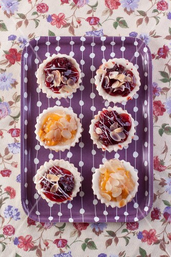 Cherry and peach tartlets on a tray (seen from above)