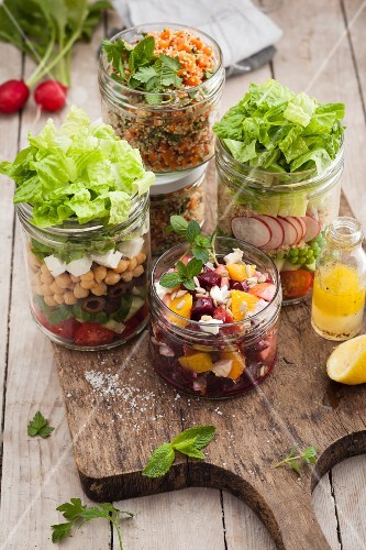 Various salads in glasses on a wooden board