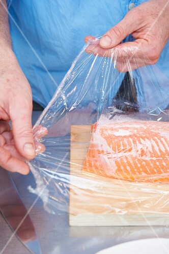 Frozen salmon trout fillet on cling film