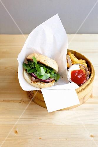 A tuna fish burger with shiso, red onions, chips, ketchup and mayonnaise