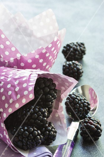 blackberries in a a pink paper bag and on a dessert spoon