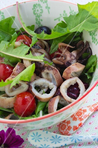 Squid salad with dandelions, olives and cherry tomatoes