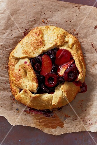 Free-form fruit pie baked on baking paper (seen from above)