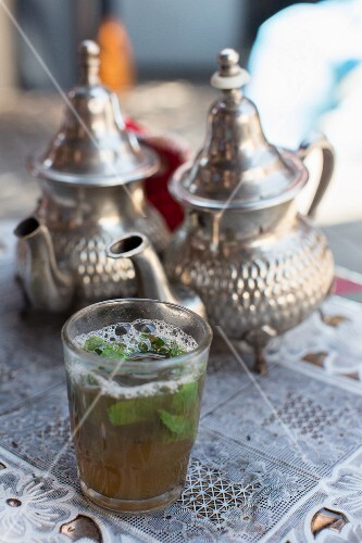 Peppermint tea in silver pots and a glass