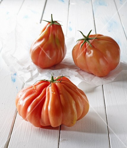 Three beefsteak tomatoes on a white wooden surface