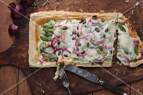 Puff pastry tart topped with goats cheese, asparagus and red onions