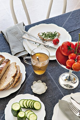 A table laid for supper with chive bread, tomatoes and herb tea
