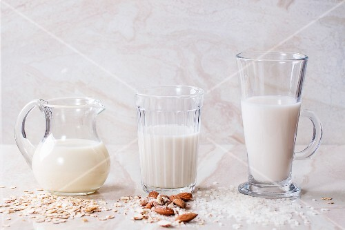 Oat milk, almond milk and rice milk on a marble surface