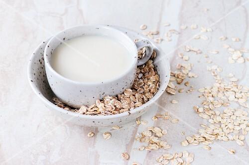 Eine Tasse Hafermilch in Schüssel mit Haferflocken auf Marmorfläche