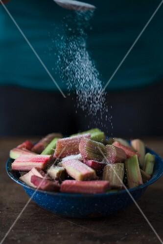 Pieces of rhubarb being sprinkled with sugar
