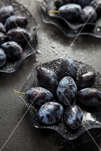 Damsons in glass bowls on a black surface