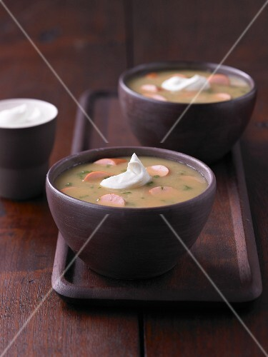 Potato soup with sliced sausages and sour cream
