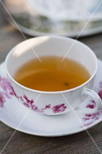Herb tea in a white teacup with a traditional wine red floral pattern