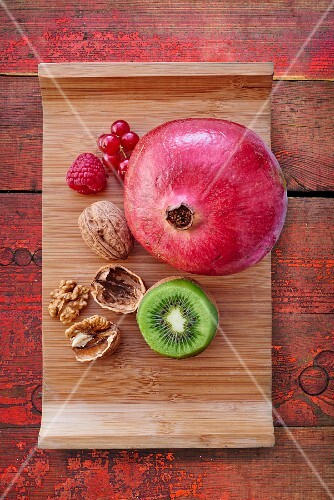 An arrangement of pomegranate, kiwi, berries and walnuts (seen from above)