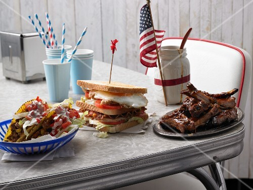 Taco shells, a club sandwich and spare ribs on a table (USA)