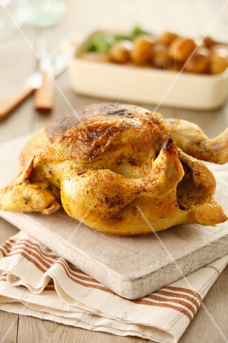 Roast chicken on a wooden chopping board