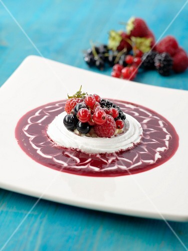 Meringue in a pool of berry sauce with fresh summer berries