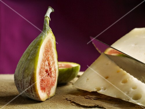 A halved fig next to a slice of cheese with a knife on a natural stone platter