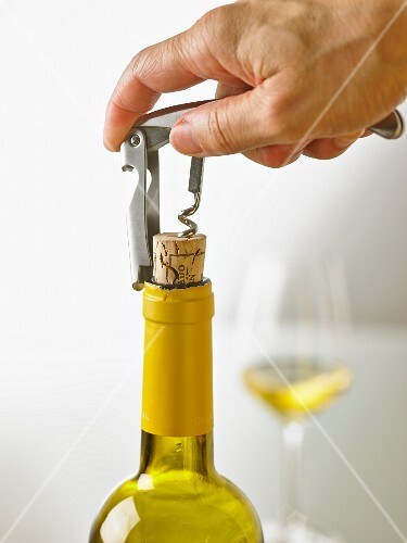 A bottle of white wine being opened with a sommelier knife