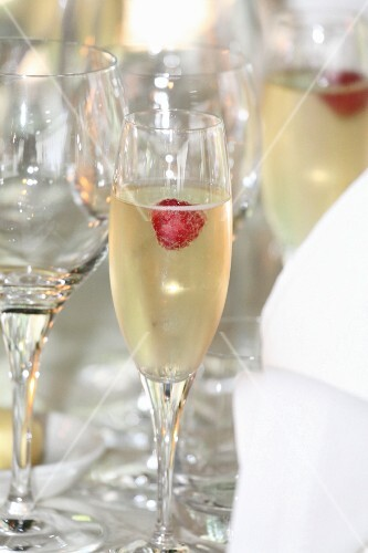 Raspberries in glasses of champagne on a table at a wedding
