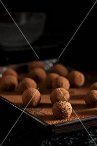 A tray of chocolate truffles being rolled in cocoa powder