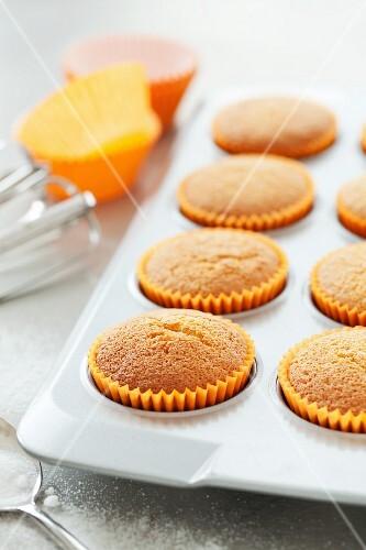 Freshly baked cupcakes in orange paper cases
